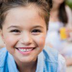 Девочка с темными волосами дарит нам свою улыбку