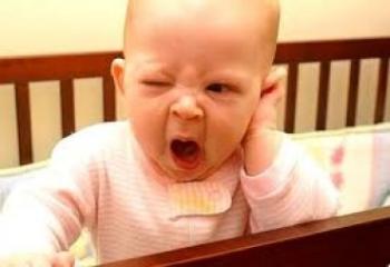 Малыш в кроватке зевает