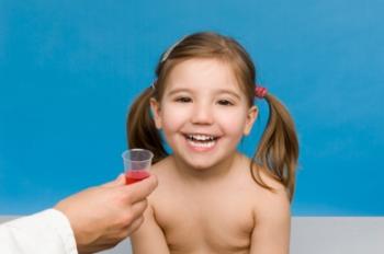 Девочке дают выпить лекарство