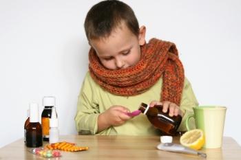 Мальчик наливает лекарство в ложку