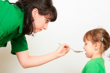 Мама дает девочке сироп