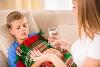 Мама дает сыну лекарство