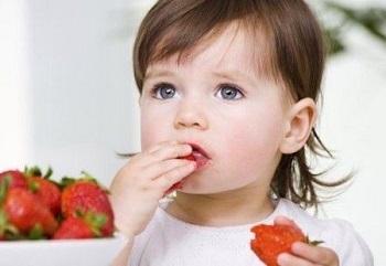 Девочка ест спелую ягоду
