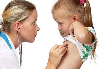 Девочку слушает врач