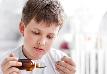Мальчик пьет лекарство