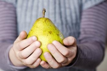 Желтая груша в руках
