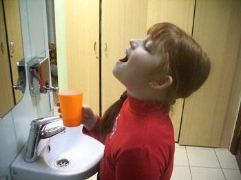 Девочка полоскает горло