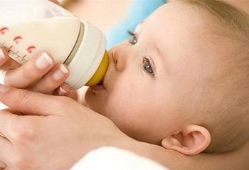 Малыша кормят из бутылочки