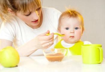 Мама кормит ребенка из ложки