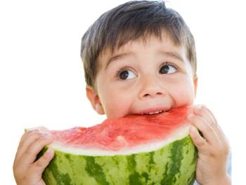Мальчик ест спелый арбуз