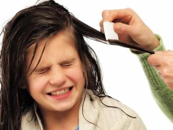 Девочке расчесывают волосы