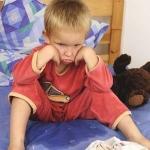 Мальчик сидит на кровати в пижаме
