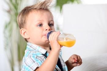 Мальчик пьет сок из бутылочки