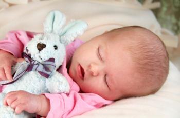 Малыш с мягкой игрушкой спит