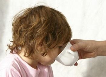 Ребенку дают попить из кружки