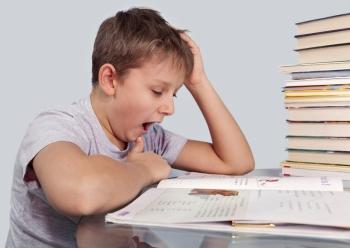 Мальчик зевает за уроками