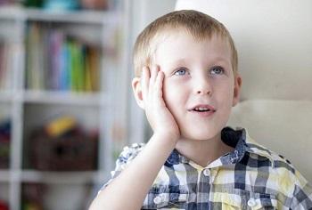 Мальчик в клетчатой рубашке задумался
