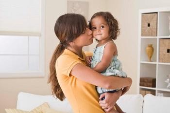 Милая девочка на руках у мамы