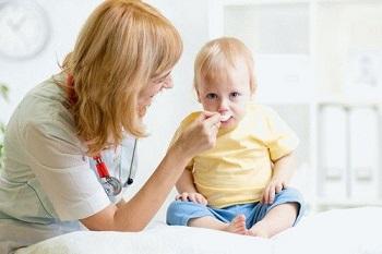 Малышу дают лекарство из ложки