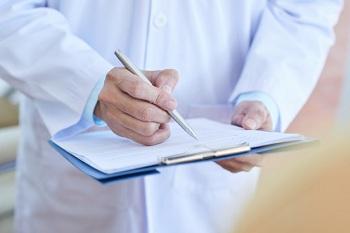 Доктор заполняет документы