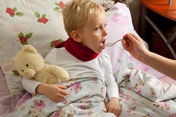 Мальчику дают лекарство из ложки