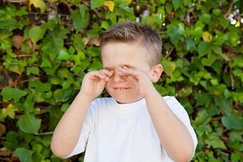 Мальчик чешет глаза руками