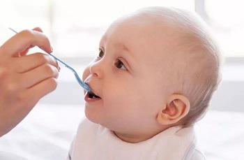 Ребенку дают лекарство из ложки
