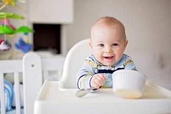 Малыш за столом с ложкой