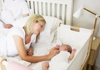 Мама смотрит на малыша в кроватке