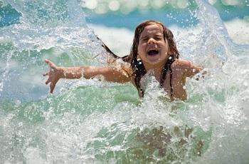 Счастливая девочка купается в море
