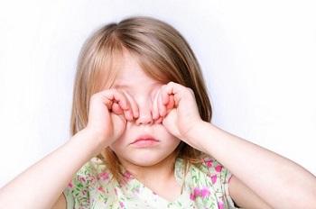 Девочка трет глаза руками