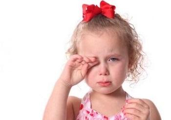 Девочка с красным бантиком плачет