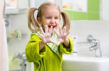 Девочка моет руки в ванной комнате