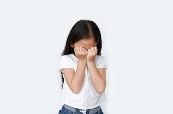 Девочка закрыла лицо руками