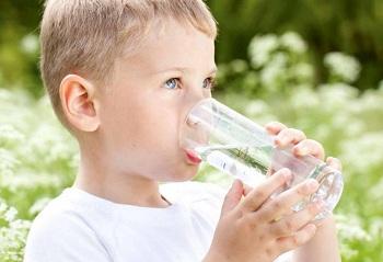 Мальчик пьет чистую воду