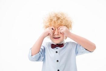 Кудрявый мальчик трет глаза