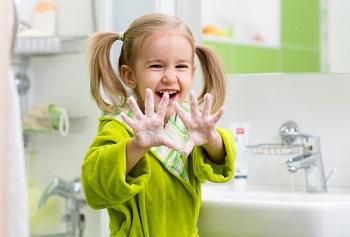 Девочка с хвостиками моет руки