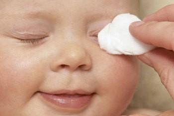 Ребенку вытирают глаза