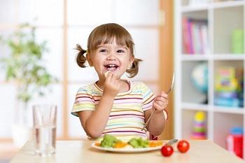 Веселая девочка обедает