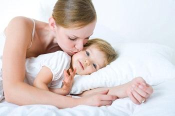 Мама обнимает и целует малыша