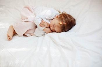 Девочка спит в своей постели
