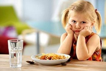 Девочка со светлыми волосами за столом