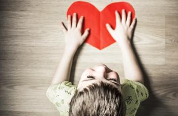 Маленький ребенок с бумажным сердцем