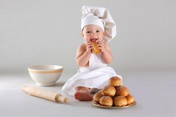 Милый малыш ест булочки