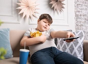 Мальчик ест и смотрит телевизор