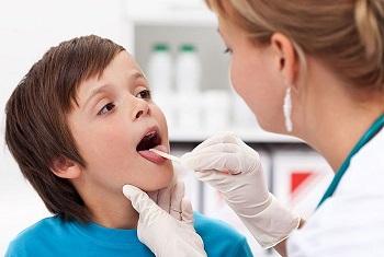 Мальчику осматривают горло