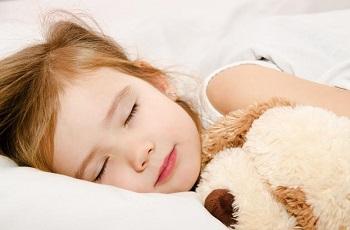Девочка спит с мягкой игрушкой