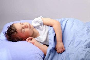 Мальчик спит в своей кровати