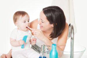 Мама чистит маленькому ребенку зубы